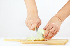 Hands with a knife slices onion on a cutting board Royalty Free Stock Images