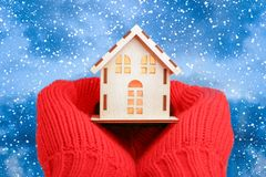 Hands in knitted mittens Holding model House on winter background. House Energy Efficiency Concept. Warm home stock photography