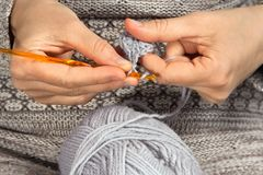 Hands knitting with crochet hook and grey yarn Stock Photography