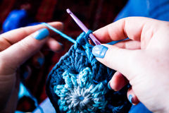 Hands Knitting / crocheting granny squares. Close up shot of a woman Knitting granny squares Royalty Free Stock Photography