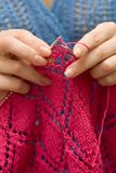 Hands knitting a red scarf on blue background Stock Photo