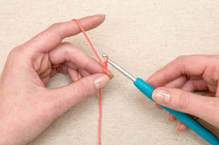 Hands Knitting a Strand of Orange Yarn with Knitting Needle Stock Photography