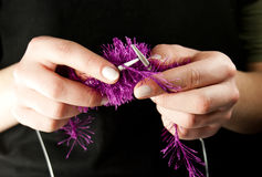 Hands knitting a thing with spokes. Isolated on black Royalty Free Stock Photo
