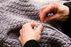 Hands and knitwear. Close-up of hands working on a piece of knitwork Royalty Free Stock Image