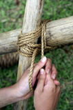 Hands knots and lashing. Female hands tying knots and lashing on wooden spars Stock Images
