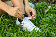 Hands lacing with bootlace the sneaker closeup Stock Image