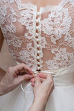 Hands lacing corset of wedding gown Stock Images