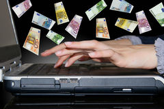Hands on Laptop. And euro rain Royalty Free Stock Images
