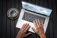 Hands Laptop Computer Business. Hands using a laptop computer from above on a black wood background with a cup of coffee and a business themed image on the Royalty Free Stock Images