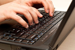 Hands on laptop keyboard. Male hands typing on a laptop keyboard. In motion royalty free stock photography