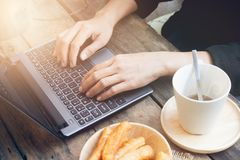Hands on laptop keyboard. Hands woman on laptop keyboard and coffee with chinese bread stick stock photography