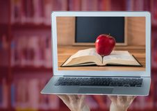 Hands with laptop showing book with red apple against blurry bookshelf with red overlay Royalty Free Stock Photo