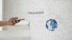 Hands launch the Earth`s hologram and Training text. Man with future technology phone is showing a 3d projection on a modern white background stock footage