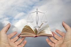 Hands of the lawyer show the scales and the book of justice. Royalty Free Stock Photography