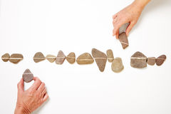 Hands laying out line with many pebbles Stock Photography