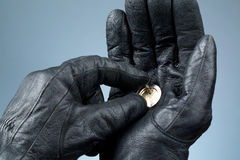 Hands with leather gloves holding money. Two hands with leather gloves holding a broken Euro coin. Concept of theft, crisis, stress, financial problems Stock Photo