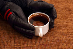 Hands in leather gloves next to a hot cup of coffee Stock Images