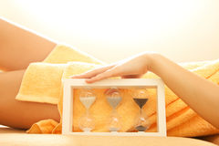 Hands and legs in spa salon with a sandglass Stock Photos