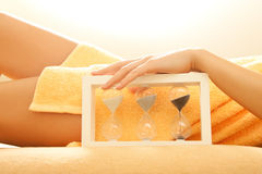 Hands and legs in spa salon with a sandglass. Closeup picture of female hands and legs in spa salon with a sandglass Stock Image