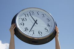 Hands lifting big clock outdoors Royalty Free Stock Photos