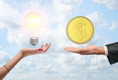 Hands with light bulb and gold coin on cloud background Stock Photo