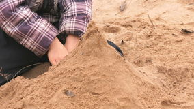 Hands of little boy playing with sand. Hands of little boy in checkered jacket playing with sand and learning how to make shapes in outdoor sandbox. Close-up stock footage