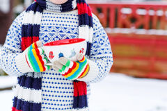 Hands of little child holding big cup with snowflakes and hot ch Stock Photography