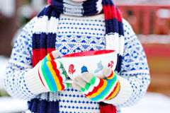 Hands of little child holding big cup with snowflakes and hot ch Stock Photo