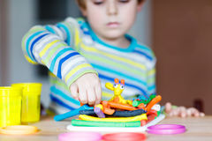Hands of little child playing with dough, colorful modeling comp Royalty Free Stock Photography