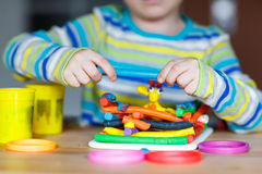 Hands of little child playing with dough, colorful modeling comp Royalty Free Stock Images