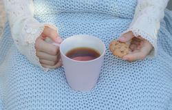 Hands of little girl in cozy hand warmers fingerless gloves holding cup of tea and cookie. On her knees wrapped in warm knitted plaid. Hugge or lagom style stock image