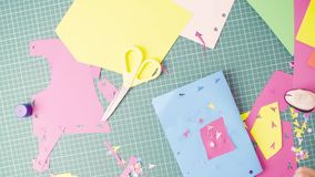 Hands of little girl gluing colored paper stock footage
