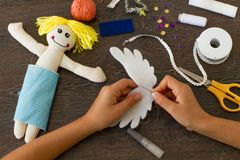 Hands of little girl making a rag doll. Child making a felt angel doll with sewing supplies on wooden table Royalty Free Stock Photo