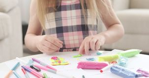 Hands of little girl molding colorful plasticine. At home stock video