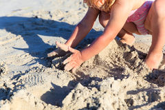 Hands of little girl play with sand on beach Stock Image