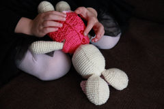 Hands of little girl playing with Easter crochet bunny Stock Photo