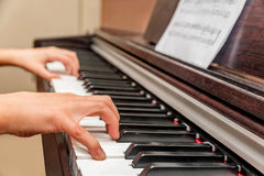 Hands of a little girl playing the piano Stock Image