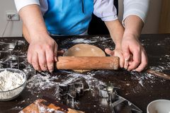 Hands of little girl sheeting dough with rolling pin. Christmas baking preparation. Child`s hands with a rolling pin baking Christmas gingerbread cookies Stock Image