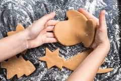 Hands of little girl sheeting dough with rolling pin. Christmas baking preparation. Child`s hands with a rolling pin baking Christmas gingerbread cookies Royalty Free Stock Image
