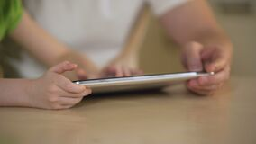 Hands of little girl typing on tablet touchscreen, father and daughter using app. Stock footage stock video footage