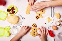 The hands of a little girlish girl and mother make a pastry cookie. Christmas baking. Christmas gingerbread in the shape of stock photo
