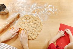 Little kid boy helps mother to cook ginger biscuit. Happy family mom and child in weekend morning at home. Relationship. The hands of little kid boy who helps royalty free stock image