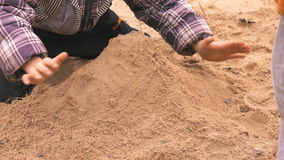 hands of little kid playing with sand in checkered jacket and learning how to make shapes in outdoor sandbox close up stock footage