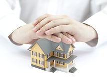 Hands and little yellow house Stock Image