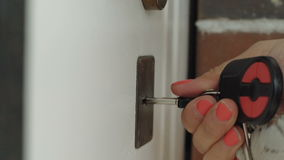 Hands Locking The Door With Key. Female hand puts the key in the keyhole stock footage