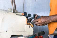 The hands of a locksmith copying a key with a machine in Galle, Sri Lanka.  royalty free stock photo