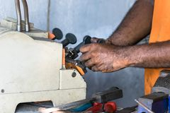 The hands of a locksmith copying a key with a machine in Galle, Sri Lanka.  royalty free stock images