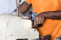 The hands of a locksmith copying a key with a machine in Galle, Sri Lanka.  stock photo