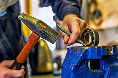 A mechanic with a hammer and a chisel works behind a workbench. Hands locksmith with a hammer and a chisel. Knocks out the bearing sandwiched in the bench on stock photo