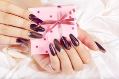 Hands with long artificial manicured nails holding a gift box Stock Photo